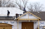 Roofers install a roof on a new construction home in Pepper Pike, Ohio.