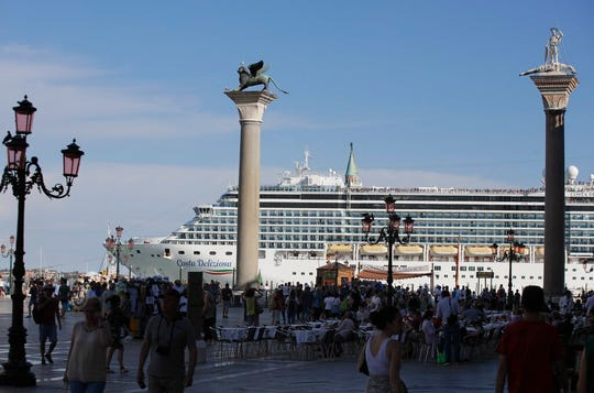 A cruise ship passes by St. Mark's Square filled with tourists, in Venice, Italy, Sunday, June 2, 2019. Groups that want to ban cruise ships on Venice's busy canals say a collision that injured four tourists has served as a wake-up call.