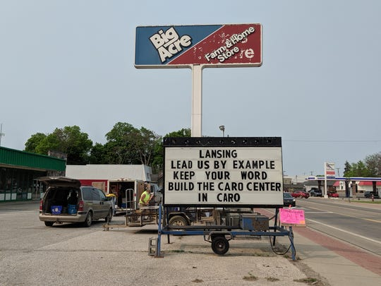 """A sign outside the Big Acre Farm & Home Store in Caro asks Lansing officials to """"keep your word"""" and rebuild a state psychiatric hospital."""