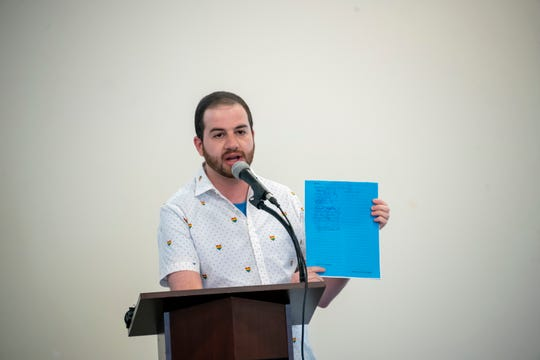 Michigan State Senator Jeremy Moss holds up a bill that would amend the Elliott-Larsen Civil Rights Act and protect LGBTQ citizens from discrimination during a pride town hall meeting at Affirmations, in Ferndale on Monday.