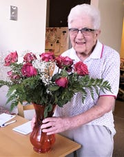 Hazel Thompson, 101, of Elmira, shows off the bouquet of flowers presented to her by the Elmira YWCA for her 70 years of volunteering.