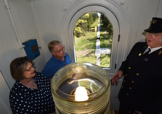 Baileys Harbor Range Lights docent Ed Miller, right, portrays lightkeeper Henry Gattie as he leads a tour for Mark and Candie Jurovic of Sun Prairie in the Upper Range Light at The Ridges Sanctuary.