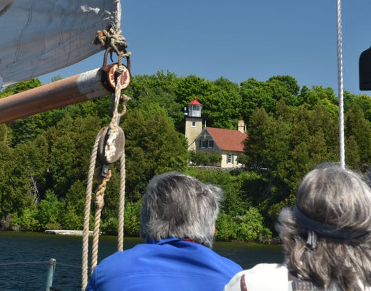 Guests take in a view from the bay of Green Bay of Eagle Bluff Lighthouse inside Peninsula State Park aboard the schooner Edith M. Becker during the Door County Lighthouse Festival.