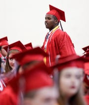 Mohamed Amin Mohamed walks through the rows of Green Bay East High School graduates before the start of the school's commencement ceremony on Sunday at the Kress Center in Green Bay.