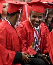 Mohamed Amin Mohamed, right, talks with fellow Green Bay East High School graduates before the start of the school's commencement ceremony on Sunday at the Kress Center in Green Bay.