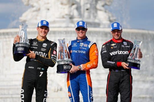 From left to right, Marcus Ericsson, of Sweden, third place finisher; Scott Dixon, of New Zealand, first place; and Will Power (12), of Australia, second place, celebrate after with their trophies after the second race of the IndyCar Detroit Grand Prix auto racing doubleheader in Detroit, Sunday, June 2, 2019.
