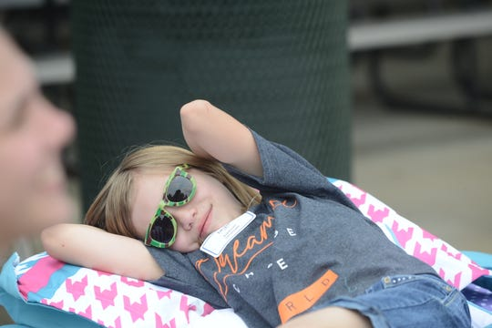 Addison Shurnate relaxes on her new bed from the Ashley Homestores Hope to Dream program at the Ballpark in Jackson on June 1 in Jackson, Tenn.