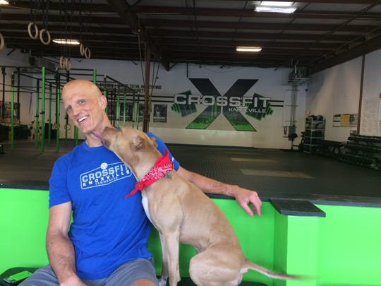 Crossfit Knoxville founder/owner Johnny Davis and gym mascot Dewey, a 4-year-old pit bull, share a moment.