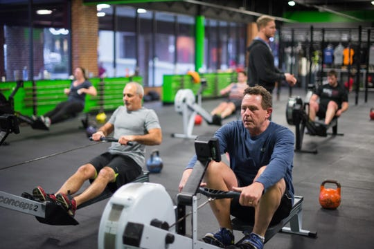 Georges Brandon, left, and Andy Lorenz get their workouts on a rowing machine.