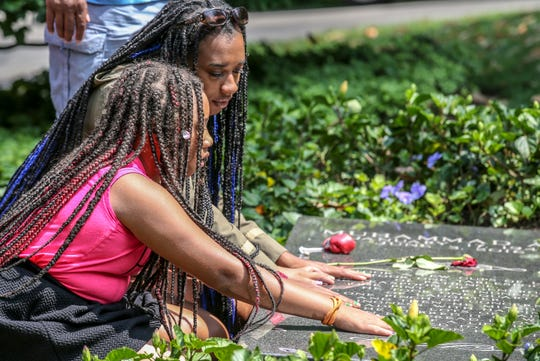 Devyn and Deja Davenport place their hands on the grave of Muhammad Ali at Cave Hill Cemetery on the third anniversary of his death.
