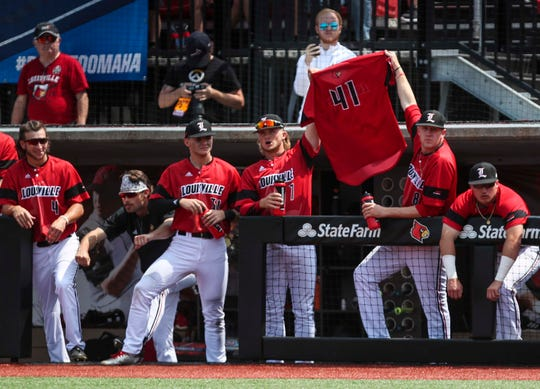 Late in the Regional against Illinois State, Louisville players Lucas Dunn, left, and Nick Bennett, right, hold up the jersey of Michael McAvene, who was ejected and suspended for four additional games after expressing his displeasure over an umpire's call Sunday in the game against Indiana. June 3, 2019.