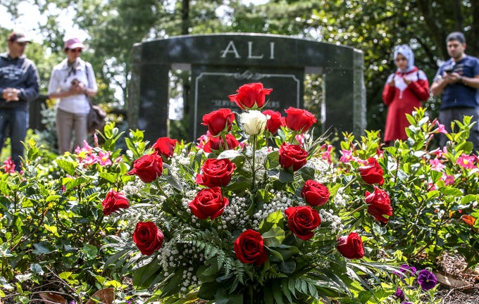 A steady stream of people visited the grave of Muhammad Ali at Cave Hill Cemetery on the third anniversary of his death.  Friederrike Krenzke, Johnny Wright, Tugba Kaplan and Yunus Kaplan are in the background.