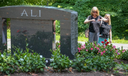 Eileen Kaelin, right, visits the grave of Muhammad Ali on the third anniversary of his death,  in Cave Hill Cemetery with her sister, Kathy Moerschell, left, who is visiting from Oregon.