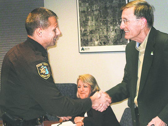 During his last board meeting as Delta Township supervisor, Joe Drolett (right) shakes hands with Lt. Jeff Warder of the Delta substation in December 2008. Drolett was instrumental in expanding the Delta patrol during his 32 years with the township. In back is former trustee Jan Cunningham.