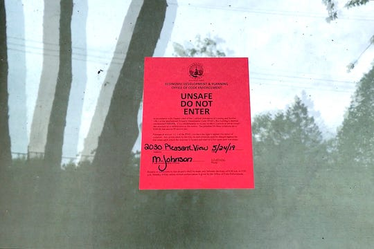 Lansing code officer Meredith Johnson red tagged a house in the 2000 block of Pleasant View Avenue indicating it's unsafe for habitation during a premise inspection on Friday, May 24, 2019, in Lansing.