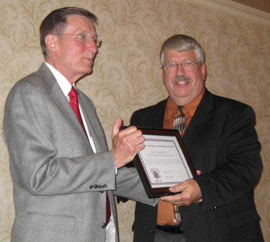 Former Delta Township supervisor Joe Drolett (left) accepts an award for his years of service from former Eaton County Sheriff Mike Raines May 14, 2009.