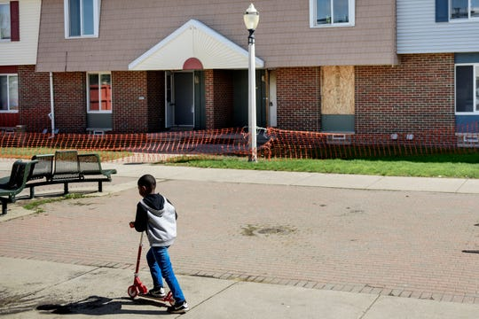 A child rides a scooter on Wednesday, May 22, 2019 in front of the unit where a fatal fire took place last June, at LaRoy Froh Townhouses, a public housing community in Lansing.