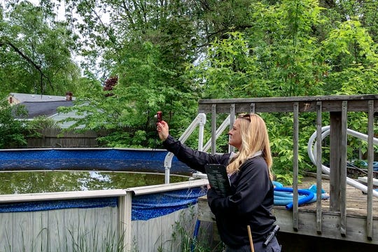Lansing code officers  Meredith Johnson takes pictures in the backyard of a house in the 2000 block of Pleasant View Avenue during a premise inspection on Friday, May 24, 2019, in Lansing.