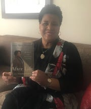 Alice Marie Johnson, the Memphis mother whose sentence on drug conspiracy charges was commuted last year by President Trump, holds up a copy of her book, After Life. Johnson is the Catalyst for Change speaker at the National Civil Rights Museum.