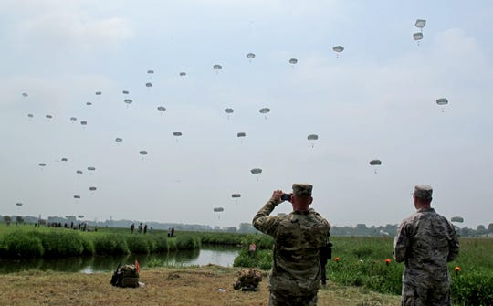 Dozens of parachutists in World War II paratrooper replica uniforms and gear fill the skies near Ste. Mere-Eglise in 2016 in commemoration of the D-Day invasion.