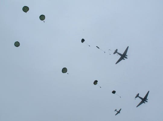 World War II re-enactors from the Round Canopy Parachute Team jump from two C-47 planes painted as they were during the D-Day invasion during a large Airborne assault re-enactment outside Ste. Mere-Eglise in 2016.