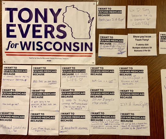 Gov. Tony Evers' political campaign hang Democrats' reasons to support Evers' proposed expansion of Medicaid at the annual state Democratic Party of Wisconsin convention in Milwaukee on Saturday.