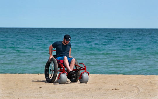 Jordan Wilkens demonstrates the use of a beach wheelchair at  Bradford Beach on Monday.