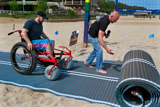 Jordan Wilkens, left, makes his way toward the water as Damian Buchman, right, rolls out a Mobi-Mat at Bradford Beach on Monday during a news conference to talk about ways of making Bradford Beach more accessible to people with disabilities.