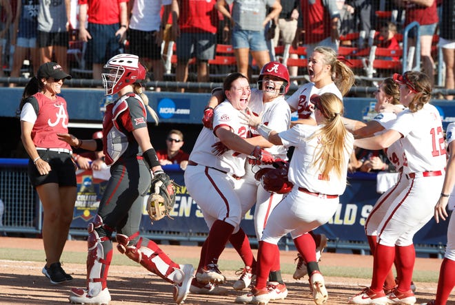 Alabama senior pinch-hitter Caroline Hardy (center) celebrates with teammates at home plate after her game-winning RBI single in the bottom of the eighth inning secured a 1-0 win over No. 1 seeded Oklahoma in the first game of Sunday's Women's College World Series national semifinal against Oklahoma on June 2, 2019 from Oklahoma City, Oklahoma. (Photo by Robert Sutton/Alabama athletics)