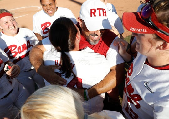 Alabama head coach Patrick Murphy hugs senior pinch-hitter Caroline Hardy (center) after her game-winning RBI single in the bottom of the eighth inning secured a 1-0 win over No. 1 seeded Oklahoma in the first game of Sunday's Women's College World Series national semifinal against Oklahoma on June 2, 2019 from Oklahoma City, Oklahoma. (Photo by Robert Sutton/Alabama athletics)