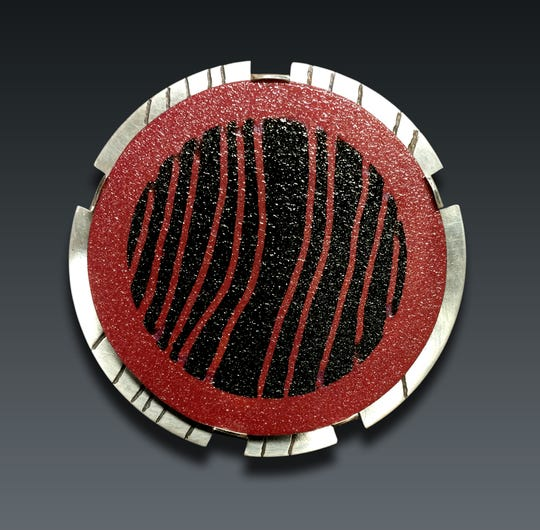 This red and black pin by Lisa Walsh will be on display durign June at Gordy Fine Art and Framing Company .