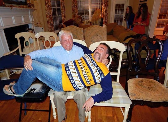 Nashville Predators President/CEO Sean Henry lies across the lap of his dad, Jerry Henry, in 2014 at the elder Henry's 80th birthday party.