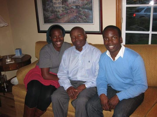 Simoni Kigweba, executive chef of Stay Golden Restaurant & Roastery, right, in 2011 with his sister, Laura, and their father, Kamana.