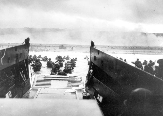 FILE - In this June 8, 1944, file photo, under heavy German machine gun fire, American infantrymen wade ashore off the ramp of a Coast Guard landing craft during the invasion of the French coast of Normandy in World War II. June 6, 2019, marks the 75th anniversary of D-Day, the assault that began the liberation of France and Europe from German occupation, leading to the end of World War II. (U.S. Coast Guard via AP, File)