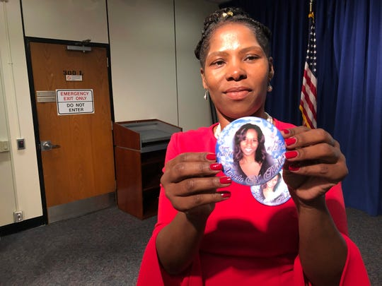 Lisa LaBoo of Eustis, Fla., holds up a button Monday depicting her sister, Angela Bledsoe, who was found shot to death in her home in Montclair in October 2018. Bledsoe's boyfriend, James Ray III, has been charged with murder. He was arrested last fall after fleeing to Cuba. (AP Photo/ David Porter)