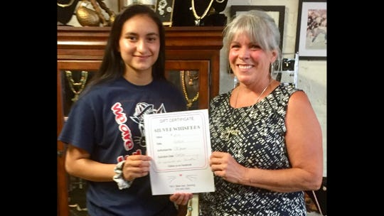 Samantha Jurado, 14, is presented with her gift certificate to Silver Whisker Thrift Store following her rescue of a four-week old kitten. Presenting the gift is Debbie Troyer