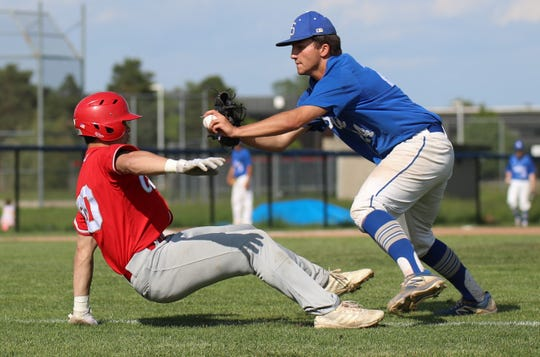 Canton's Marco Johnson is tagged out by Salem's Owen Keyes following a successful squeeze bunt.
