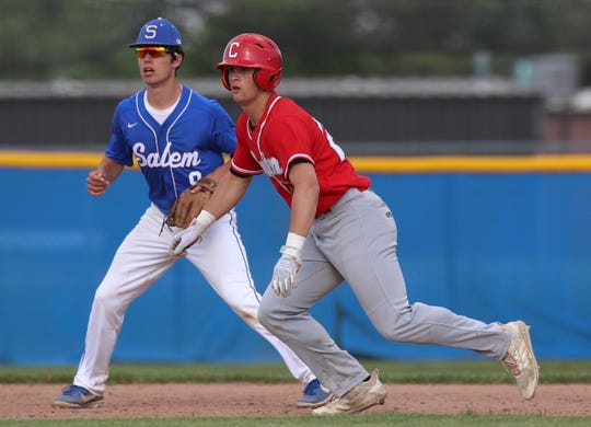 Canton's Marco Johnson and Salem's Matthew Claerhout follow the pitch.