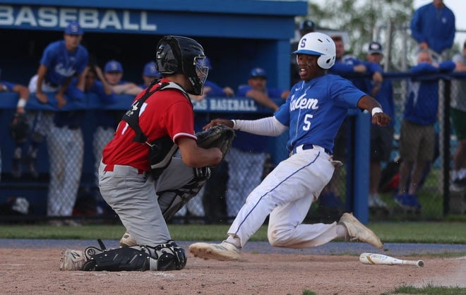 Salem's Carlton Harper slides into home plate with a run.