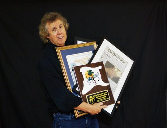 Bruce Fessier with a handful of awards and mementos he picked up during the last week before his retirement from The Desert Sun.