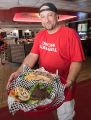 Martin Saybe, owner of the new Chicago Bar & Grill, serves up two of the new restaurant's signature items, a Chicago-style burger and an Italian beef sandwich served wet on Monday.