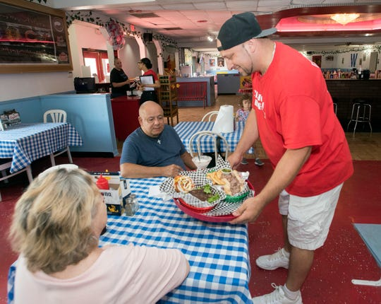 Martin Saybe, the owner of the new Chicago Bar and Grill, serves up two of the new restaurants signature items, a Chicago-style burger and an Italian beef sandwich served wet on Monday, June 3, 2019.