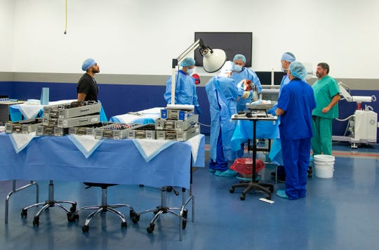 A medical team uses Research for Life's surgical room to study a human shoulder.