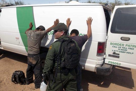 Un miembro de la Patrulla Fronteriza registra a dos jóvenes mexicanos antes de subirlos a la camioneta.