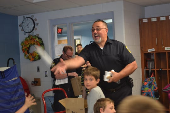 Woodville Police Chief Roy Whitehead tosses ice cream to a student at Woodmore. The officers served free ice cream to over 700 kids.
