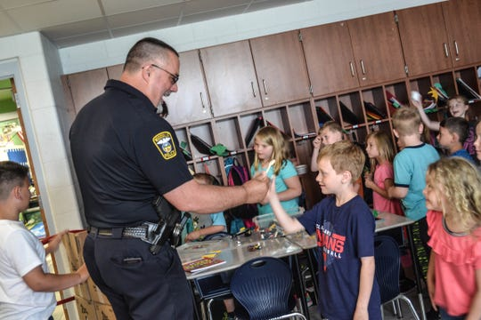 Woodville Police Chief Roy Whitehead greets a Woodmore student as he and other police officers pass out free ice cream at the school on May 30.