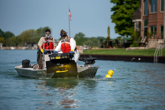 U.S. Fish and Wildlife Biological Science Technician John Ewalt, left, pilots a boat while Autumn Wiese uses a hopper to spread granular bayluscide in the St. Clair River in Algonac Friday, May 31, 2019. Once the chemical is sprayed into the water, it agitates sea lampreys, causing them to leave their nest and come to the surface.