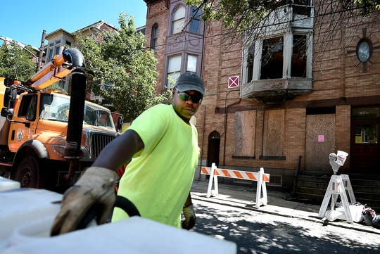 York City Public Works Highway Bureau employee Jay Johnson fills barricades with water as crews blocked off the left, westbound lane of East Philadephia Street Monday, June 3, 2019. The closure is due to a partial structure collapse on a building, background, which had burned. Portions of the sidewalk in that area will also be closed. Bill Kalina photo
