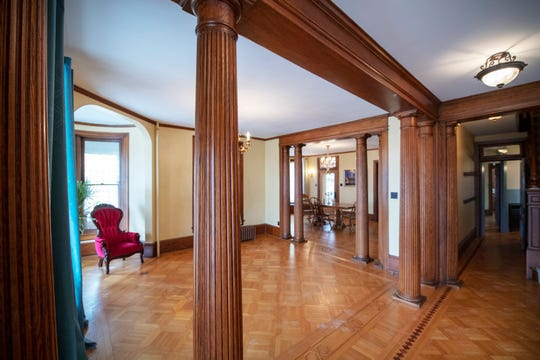 This is looking from the entryway of the former Kaltreider home through wooden pillars across inlaid wood floor.