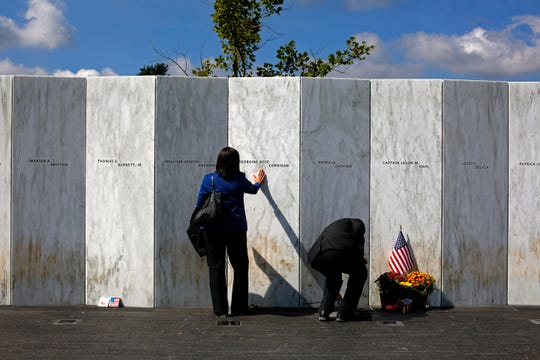 A visitor pauses at the Wall of Names after a Service of Remembrance at the Flight 93 National Memorial in Shanksville, Pa, Friday, Sept. 11, 2015. Hundreds of victims' relatives gathered for what has become a tradition of tolling bells, moments of silence and the reading of the names of the nearly 3,000 people killed in the terror strikes at the World Trade Center, the Pentagon and a field near Shanksville, Pennsylvania. (AP Photo/Gene J. Puskar)
